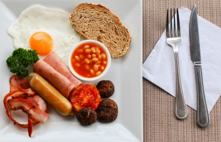 bacon baked beans: English breakfast, with bacon, sausages, a fried egg, baked beans,ham,mushrooms,bread and a tomato half