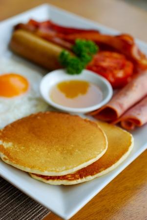 jamones: Desayuno con panqueques, salchichas, un huevo frito, dos jamones, una media de tomate, tocinos y miel