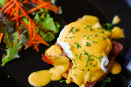 eggs benedict with salad and bacon in dishes black