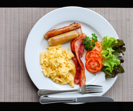 American breakfast with scrambled eggs, sausage, bacon, tomatoes and vegetables  photo