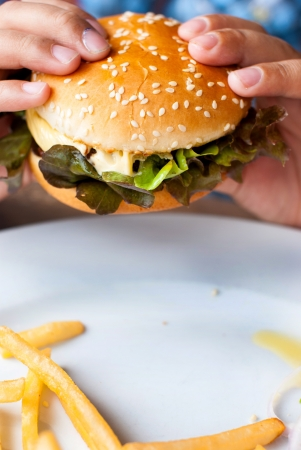 Hand holding a cheeseburger with french fries photo