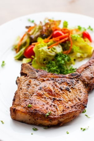 grilled pork chop: Pork chop with salad close up