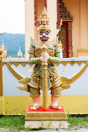 Giant statue standing in front of a buddhist temple, Bangnon in Ranong,Thailand photo