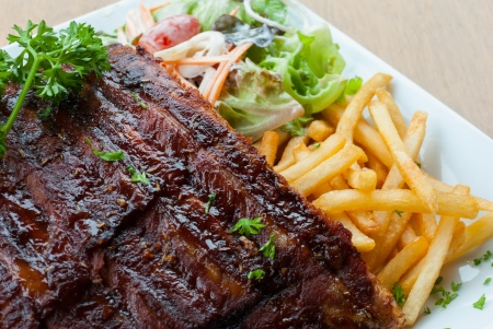 grilled juicy barbecue pork ribs in a white plate with fries and parsley  photo
