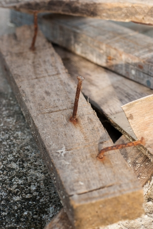 a scrap wood pile with protruding rusty nails