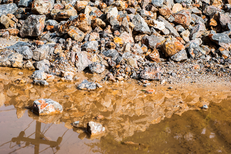 Pile of rocks  for construction  and Reflection in the water photo