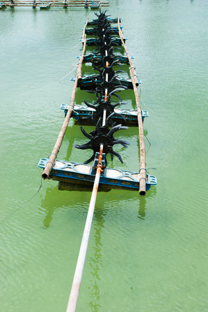Aerator on the water in the shrimp farms photo
