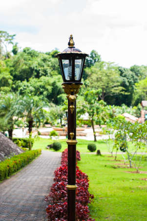 red bush: Garden lamp lined with red bush in the garden. Stock Photo