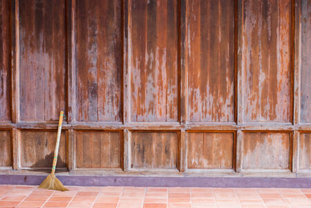Old wooden brown wall with a broom ready for cleaning work Stock Photo - 22873053