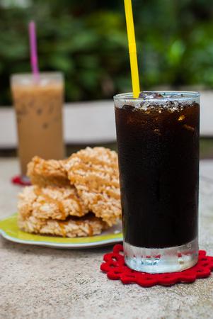 americano: Ice coffee americano with Rice Cracker  Khao Tan  on the table Stock Photo