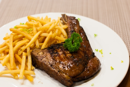 frites: Pork Chop Grilled steak with French Fries, top with parsley at restaurants