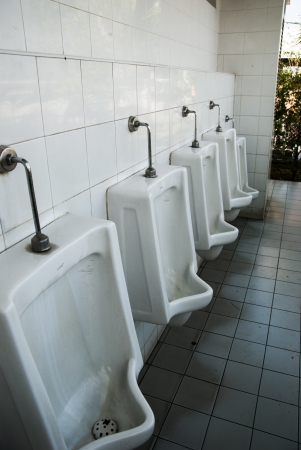 urinals in public toilets dirty photo