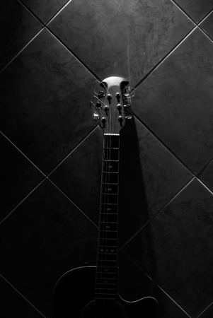 Acoustic guitar on wall tiles photo