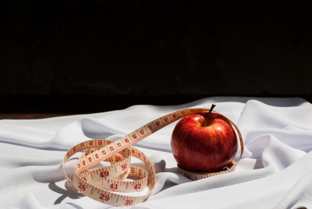 apple and a tape measure over a white background on wooden table 版權商用圖片