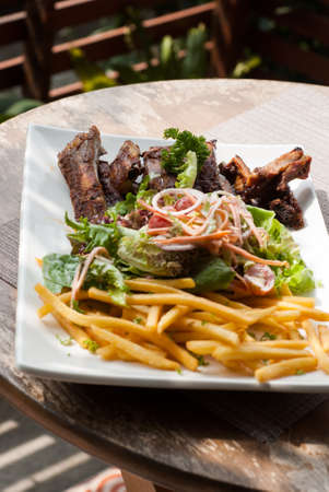 Pork spare ribs with salad and French Fries on the wooden table photo