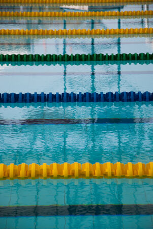 Interior of public indoor swimming pool with racing Lanes and blue water at Suphan Buri photo
