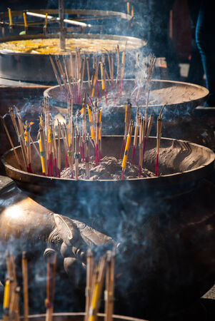 Incense sticks and smoke in ashes bucket at measured photo