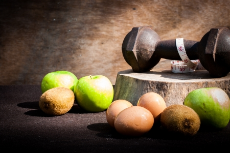 eggs , kiwi ,measuring type , apple and dumbbells for training in the morning