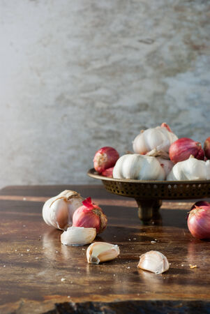 garlics: Garlic and onions in a brass tray on the wooden table Stock Photo