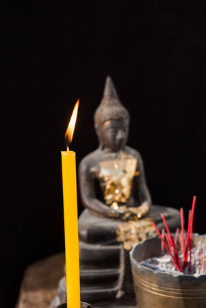 Buddha statue with incense and candles on the wooden table photo