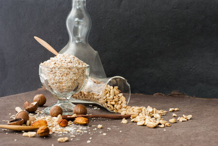 A Healthy Dry Oat meal with nut in a wooden spoon on Black background photo