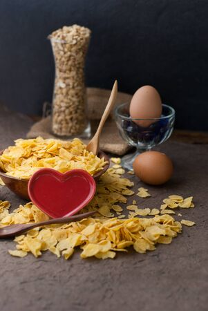 corn flakes in wooden bowl with spoons and Red heart on a table photo