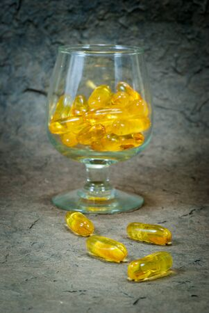 Fish oil and glass on a gray background Close up photo