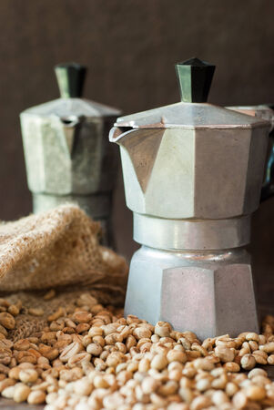 raw coffee beans with moka pot in a sack on table at morning photo