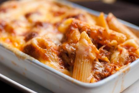 macarrones: Pasta penne al horno con salsa de tomate y queso en un taz�n blanco