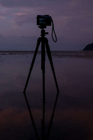 camera on the beach with reflection in water during sunset.Thailand photo