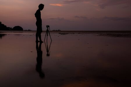 Man and camera on the beach with reflection in water during sunset.Thailand photo