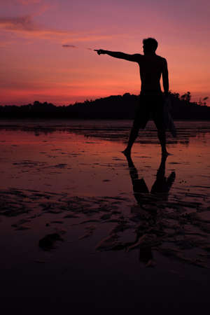 man on the beach with reflection in water during sunset.Thailand photo