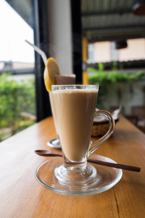 A cup of hot cappuccino with Chocolate banana smoothie and bread wooden table photo
