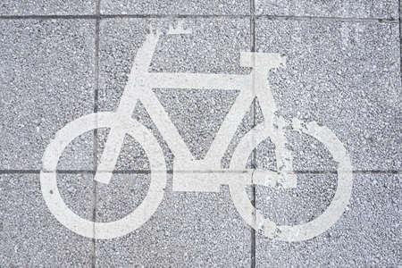 自転車レーン。暗いアスファルトの道路標示をホワイトします。 写真素材