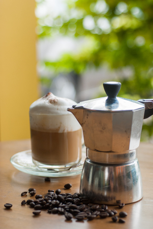 coffeemaker: a moka pot and a cup of coffee on a wooden table with roasted coffee beans