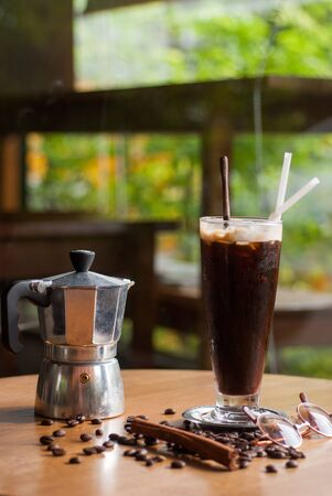 a moka pot and a cup of coffee on a wooden table with roasted coffee beans