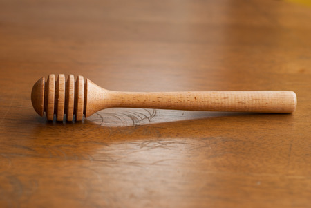 honey spoon on a wooden table , close up