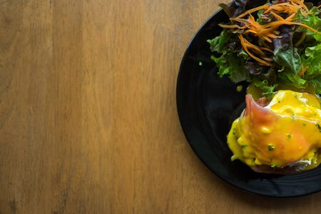 Eggs Benedict on toasted muffins with salad