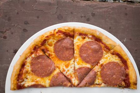 sliced salami pizza on a white plate,home made Stock Photo