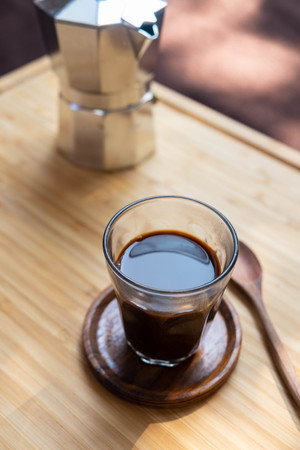 black coffee in glass with moka pot on wooden board