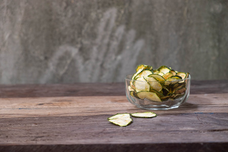 Dried zucchini in a wood bowl,chips oven baked Stock Photo