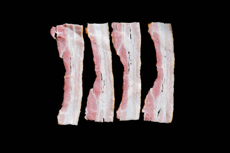 slices of fresh fried bacon in a pan for breakfast on a black background