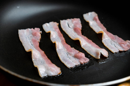 slices of fresh fried bacon in a pan for breakfast