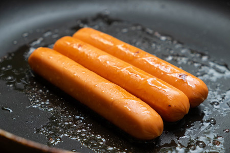 Fried sausages in a pan for breakfast Stock Photo