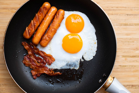 fried egg bacon and sausage in a pan