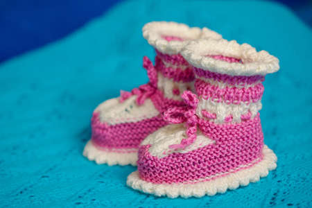 booties: Small white-pink childrens knitted booties, hand-knitted, on a wool background Stock Photo