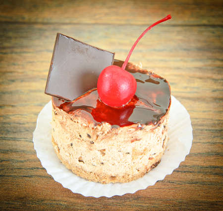 Cake with Cherries and Chocolate, Cupcake on Wood Background. Studio Photo. Stock Photo