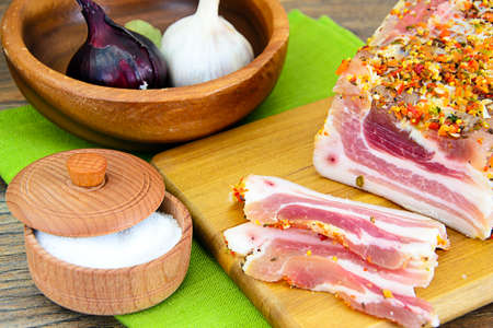 meaty: Salted Lard, Raw Pork with Spices on Wooden Cutting Board Studio Photo