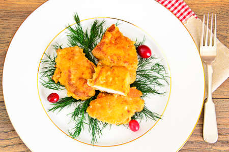 Breaded Chicken Fillet with Herbs and Cranberries. Studio Photo.