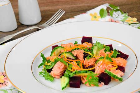 Salad with Beets, Salmon, Cucumber, Arugula, Lemon Zest, Orange, Olive Oil, Salt and Pepper on White Plate Studio Photo